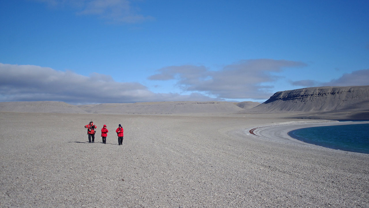 Expedition staff walk across the vegetation free expanses of Beechey Island.