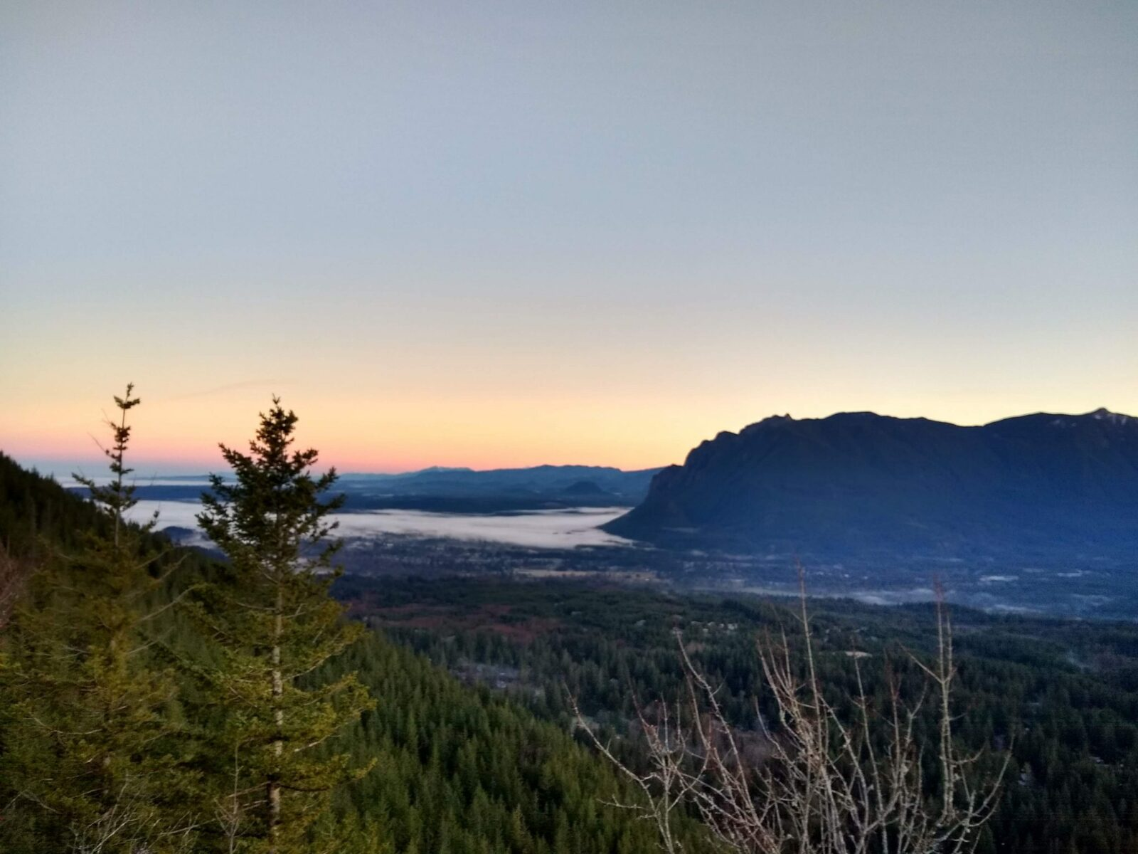 The sun is just about to rise behind a mountain from Rattlesnake ledge, a winter hike near seattle. The trees and fog in the valley is just starting to become visible and the hillsides are sillouetted.