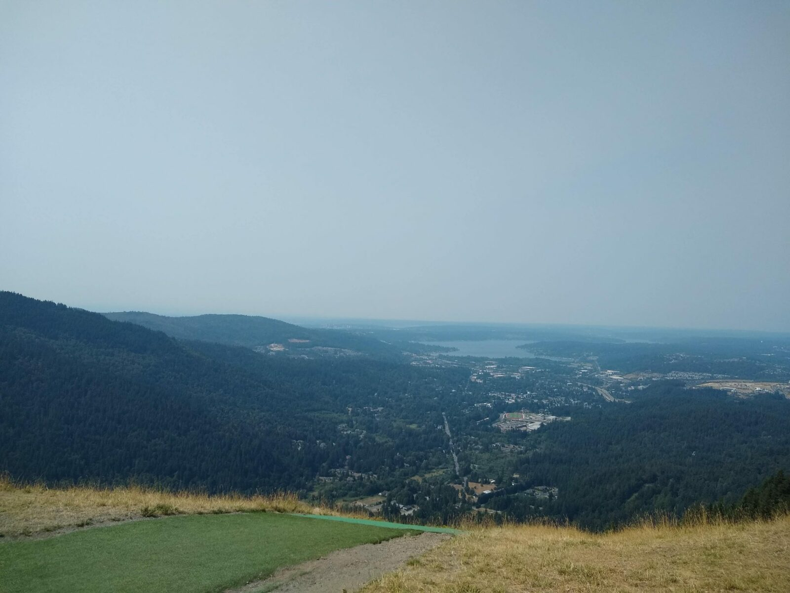 Poo Poo Point, and extremely popular hike near Issaquah. In the foreground is a green grassy areas for paragliders to launch. In the distance are forested hillsides and a town and a lake. The farther distance is obscured by haze from wildfire smoke