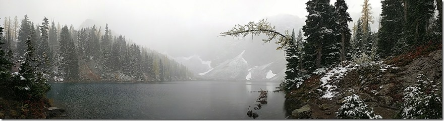 An alpine lake is surrounded by light snow on evergreen trees. It's foggy and difficult to see across the lake