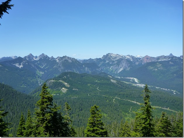 Tall mountains in the distance, smaller mountains and evergreen trees in the foreground