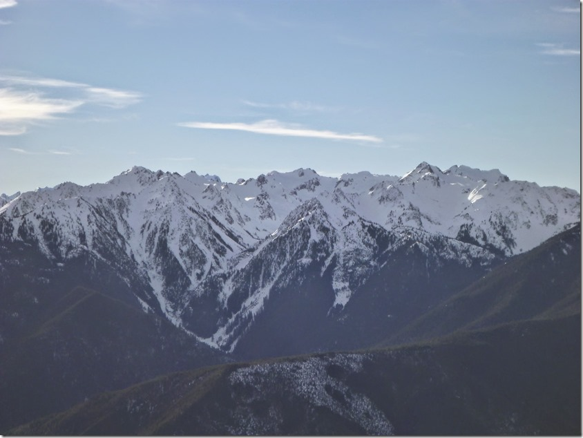Snow capped mountains seen across a valley on an Olympic National Park itinerary