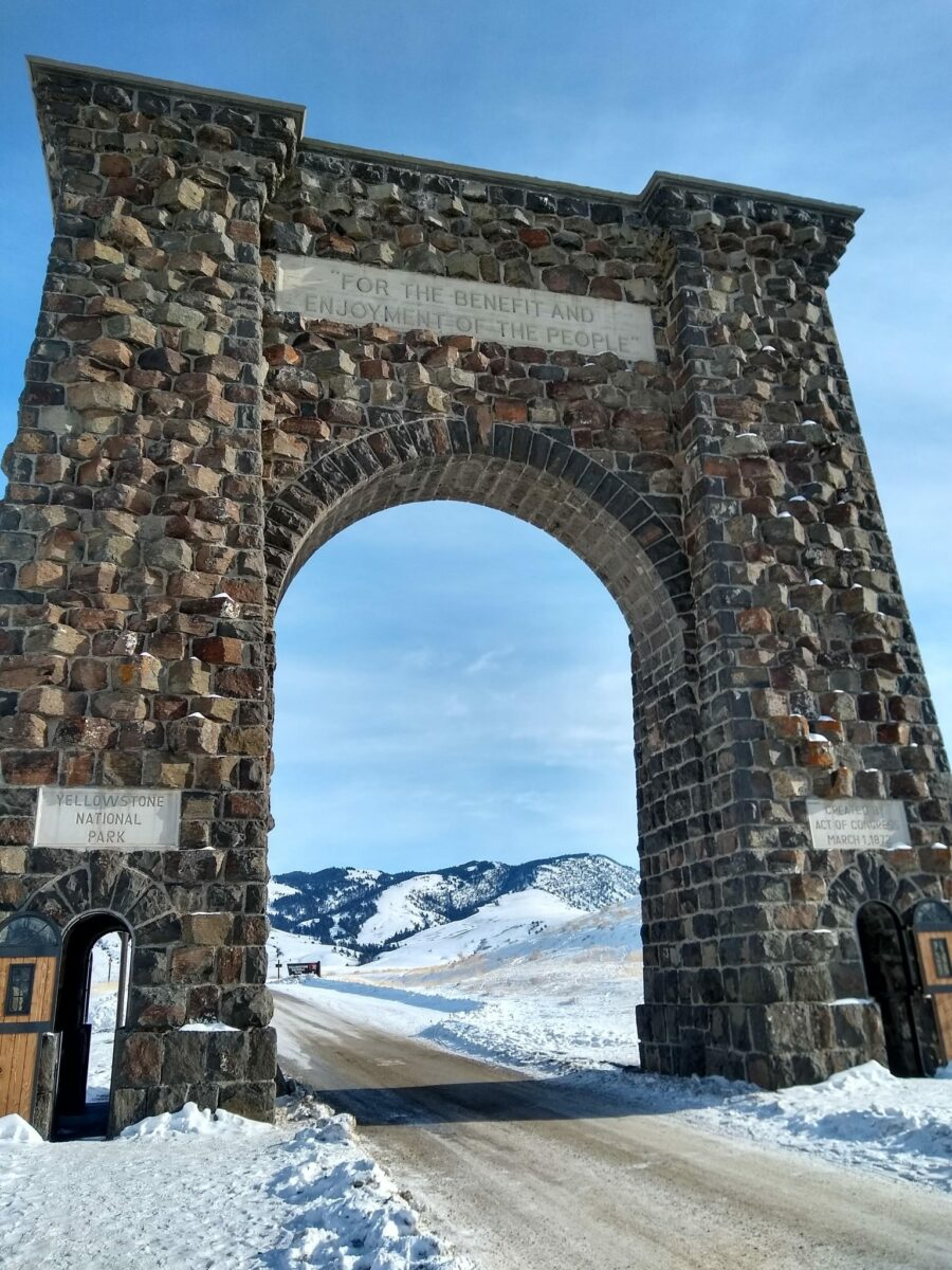 "Large stone arch over the road says Yellowstone National Park and ""For the Benefit and Enjoyment of the People"""