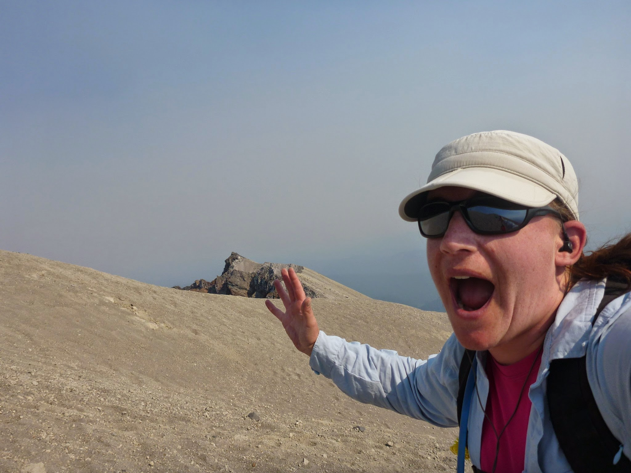 A hiker with a hand in the air, mouth open, a hat and sunglasses, near the summit of a volcano covered in sand