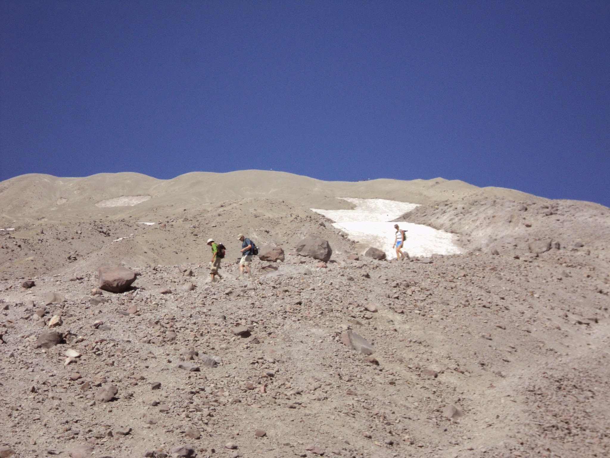 Volcanic gray sand at the top of a mountain. Three hikers walking across it. Snowfield and blue sky in the distance