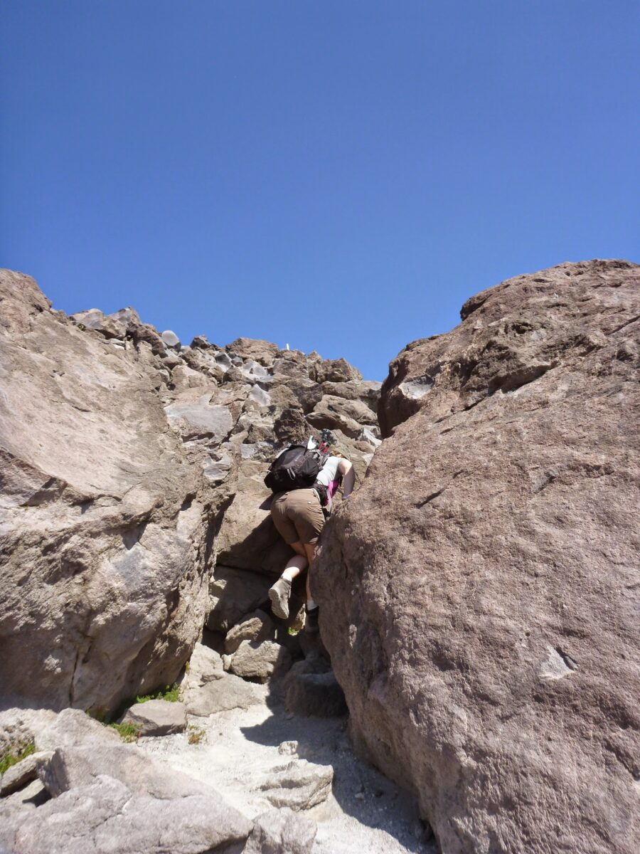 hiker climbing between two large boulders against a blue sky