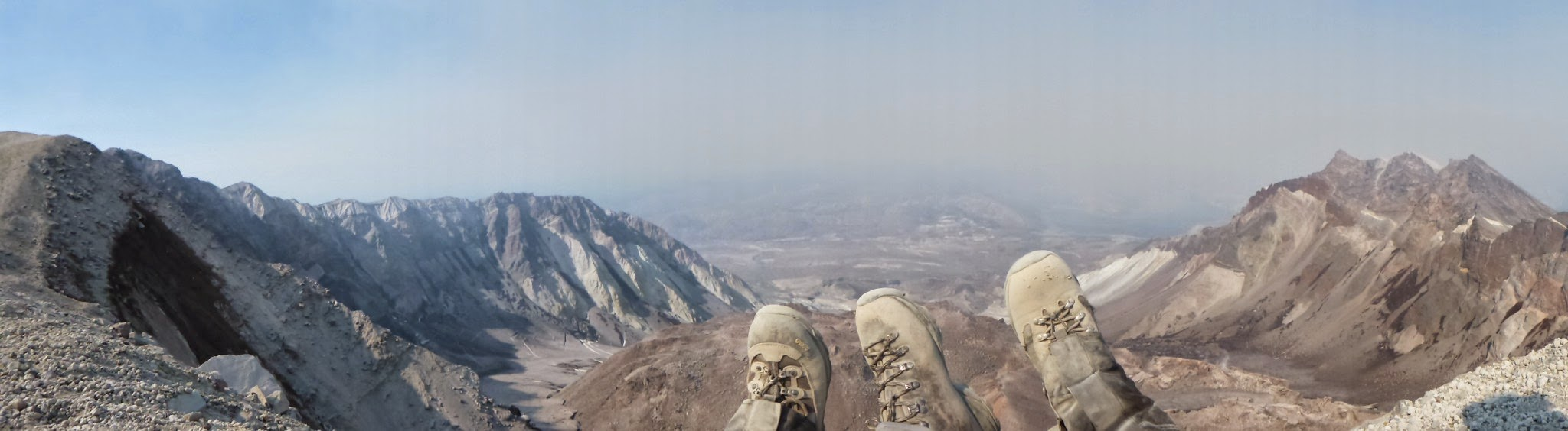 Three feet in hiking boots against a backdrop of a volcano crater, with wildfire smoke in the distance