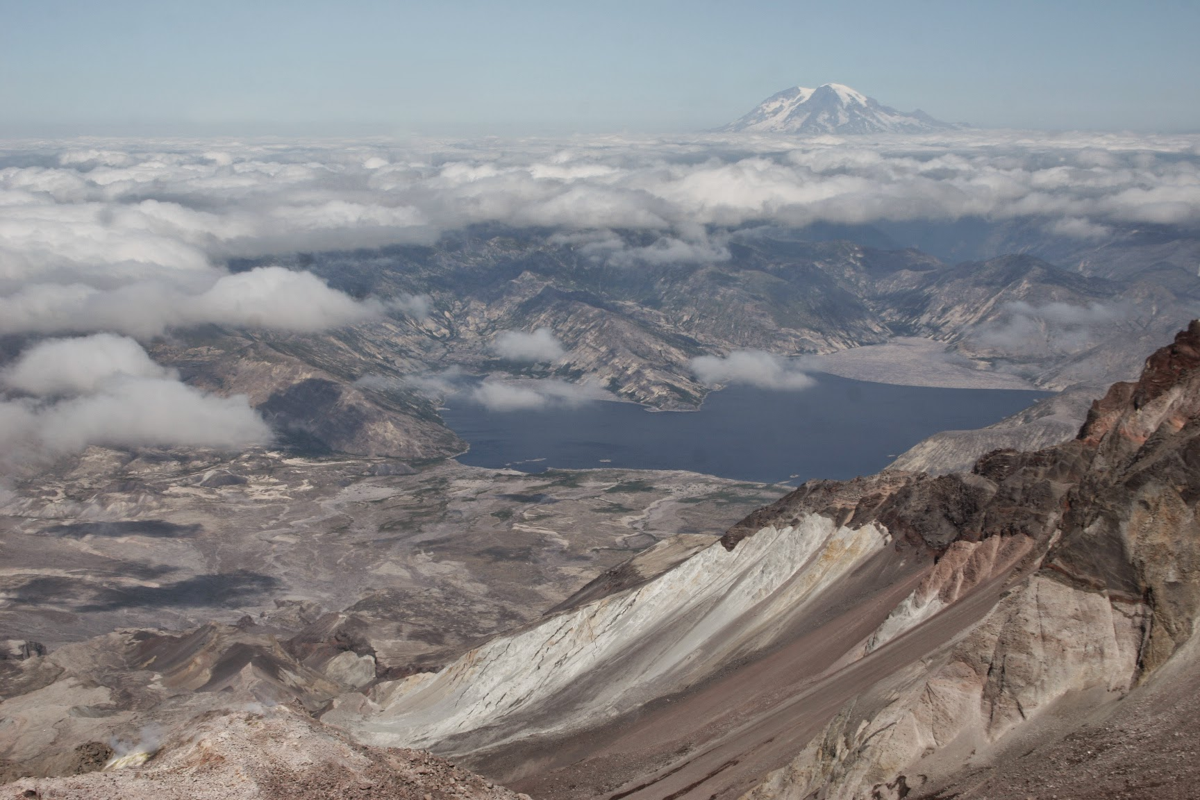 Brown volcanic crater in the foreground, a lake and hills in the distance and a high mountain in the far distance at the summit of a Mt St Helens climb