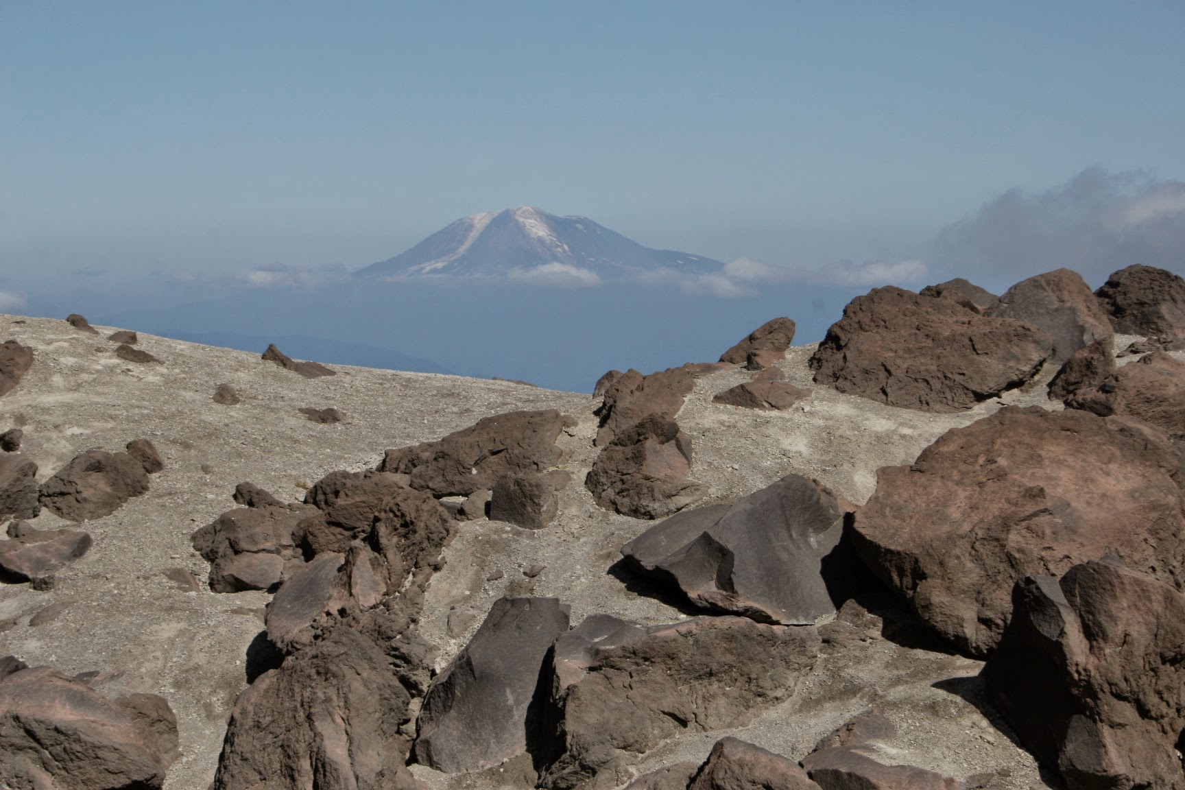 Brown rocks and volcanic sand in the foreground, a mountain and clouds in the background