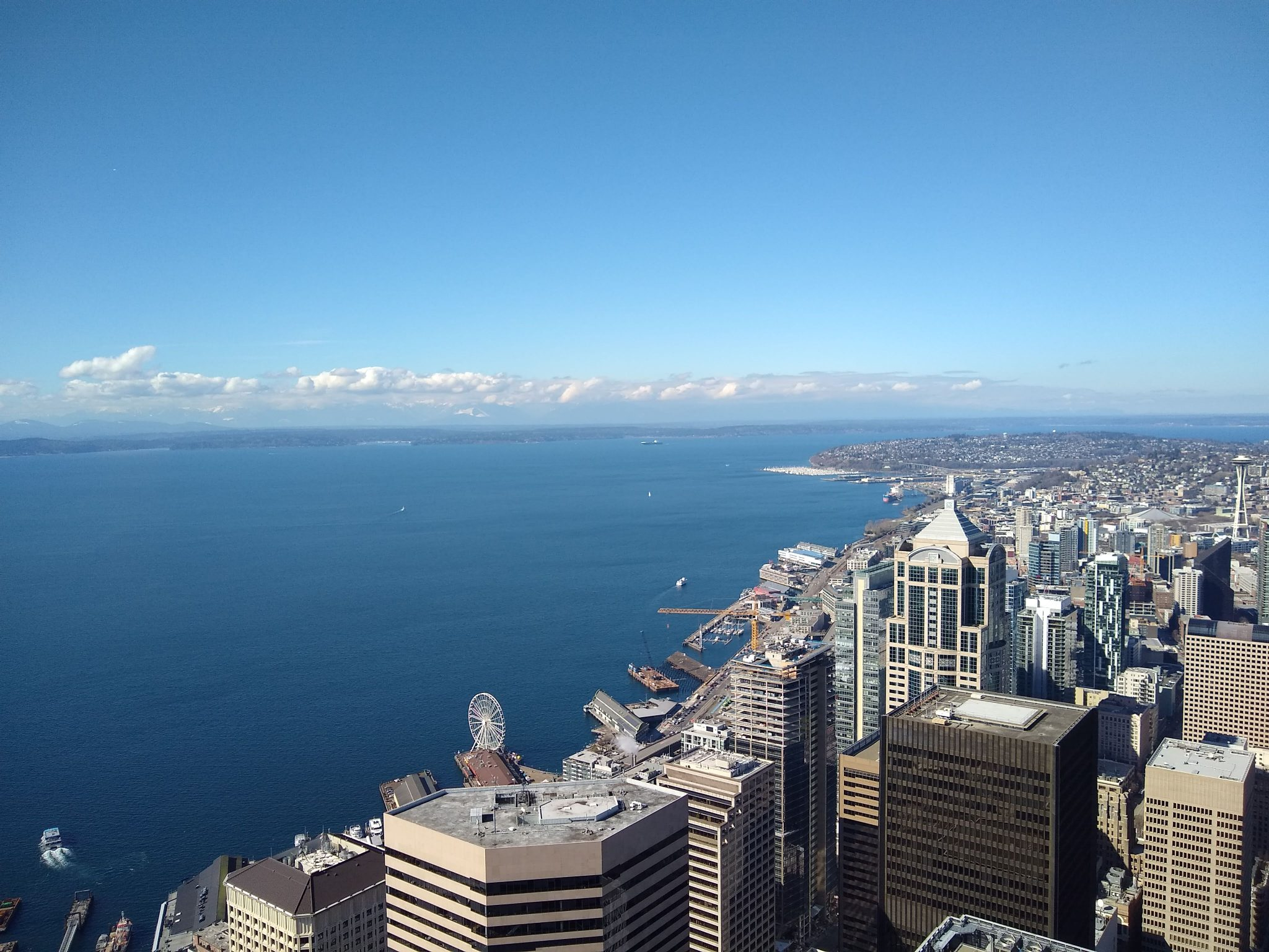 A city seen from high above. There is blue water, blue sky and some clouds above high rise buildings and a waterfront