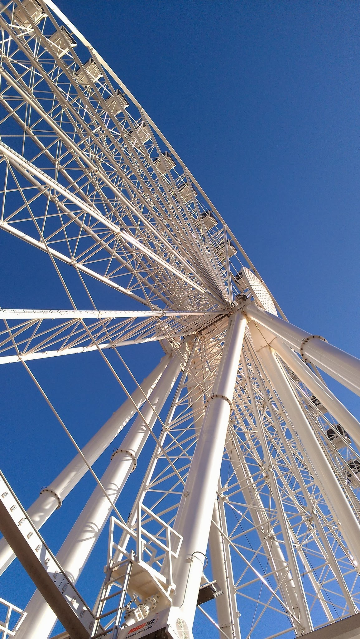 A large painted white metal ferris wheel against a blue sky
