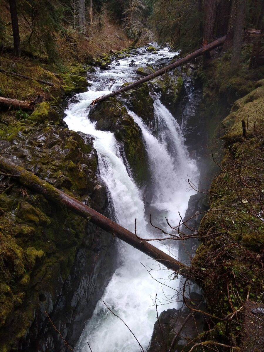 A waterfall with three falls coming down from a river above to a canyon below