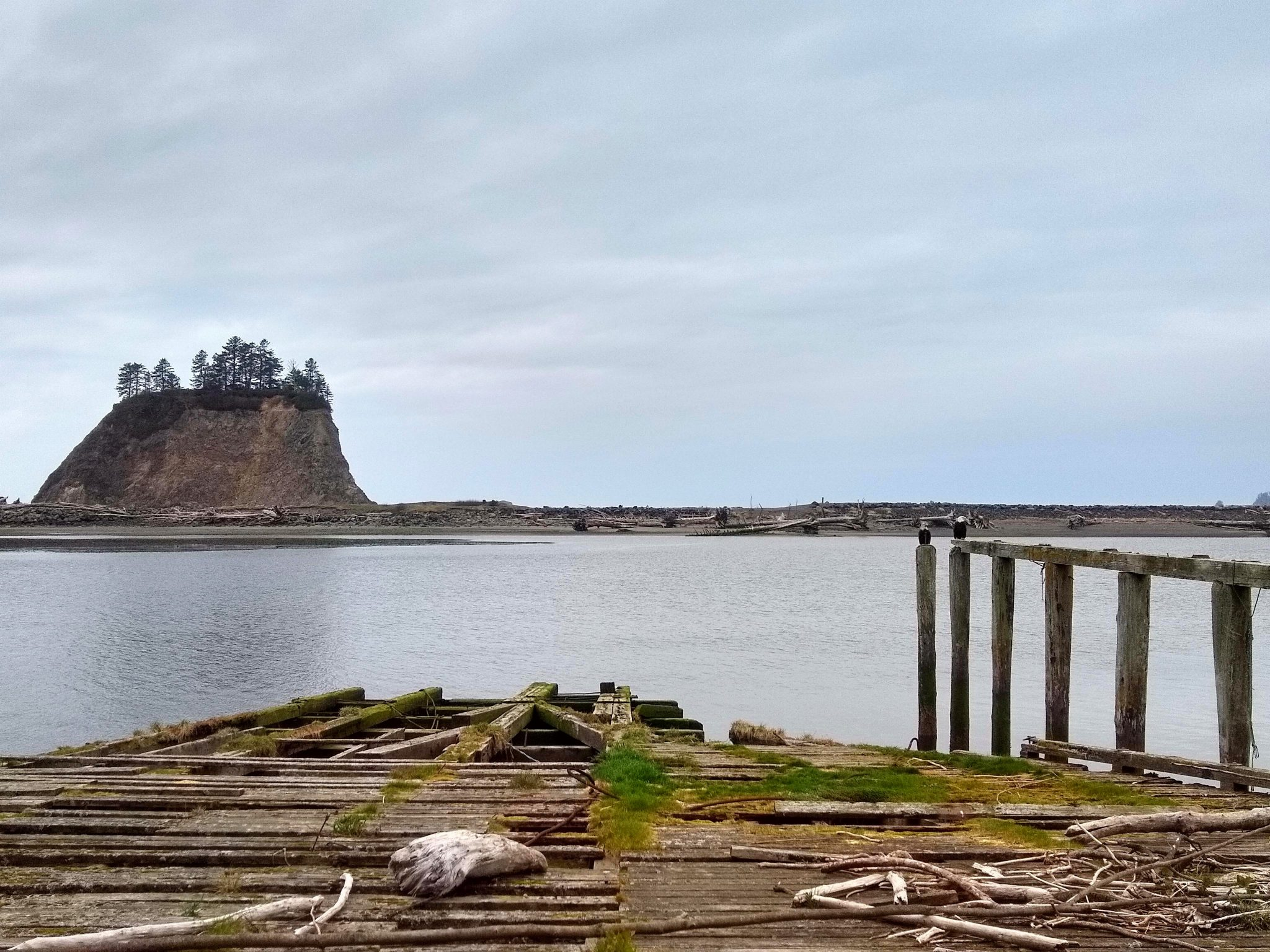A deteriorating ramp and pier. There is a small island in the distance and a beach across a bay of the Pacific Ocean. Two eagles are on the pier