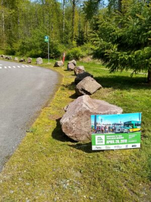 A bus stop next to boulders and a parking lot at a trailhead.