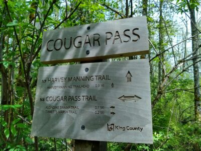A wooden sign next to a trail in the forest. The sign says Cougar Pass and shows different trails and their distance.