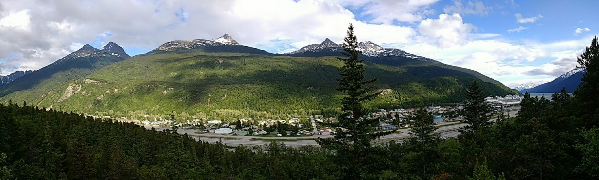 Panoramic photo of a small Alaskan town with several cruise ships in port. There are tree covered hills and snowcapped mountains in the distance. It's partly cloudy.