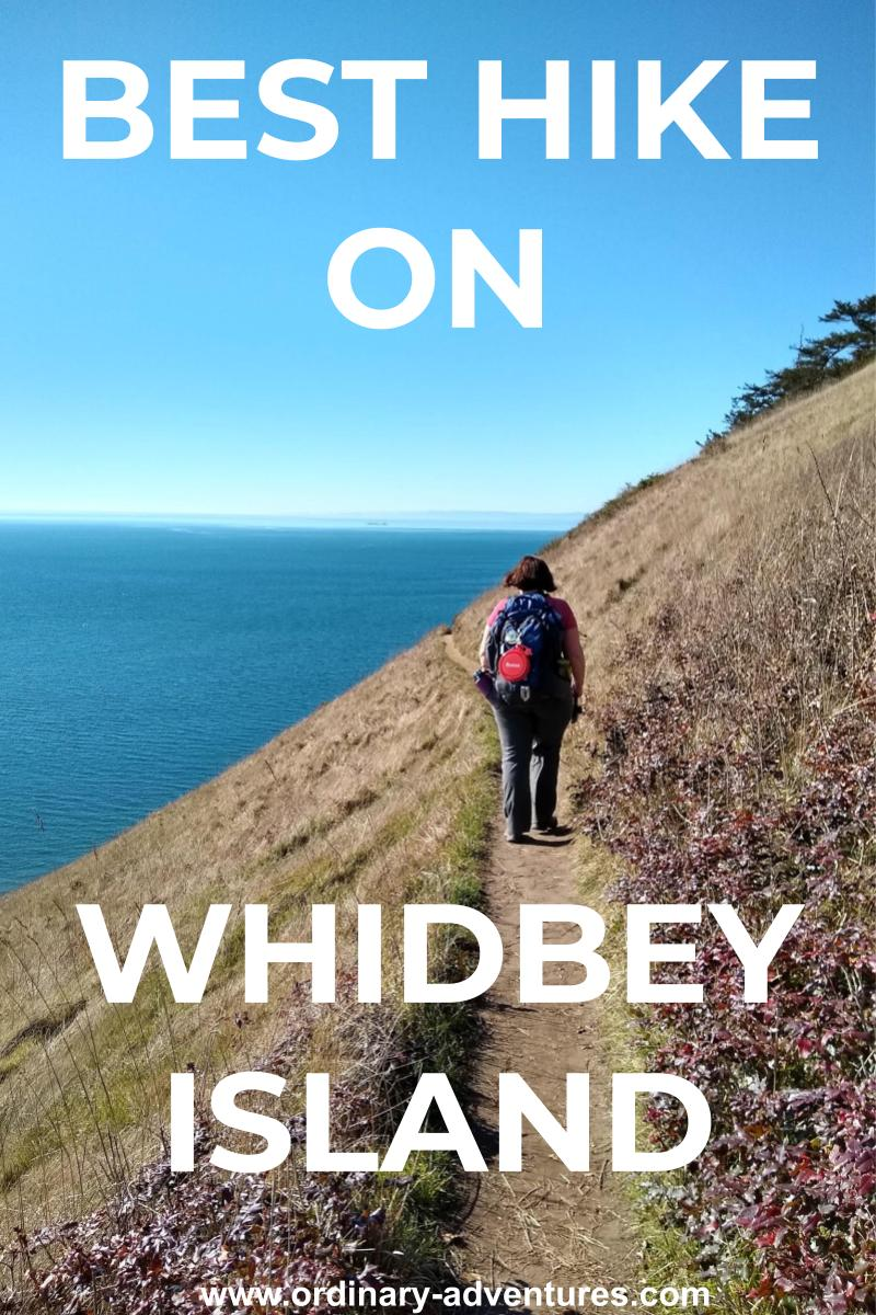 A woman is walking with her back to us on a trail on a bluff with trees to her right and blue water to her left. Distant islands are ahead of her. Text reads: Best Hike on Whidbey Island