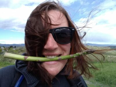 A woman wearing sunglasses is smiling and holding a single spear of asparagus in her mouth. The wind is blowing her hair from behind.