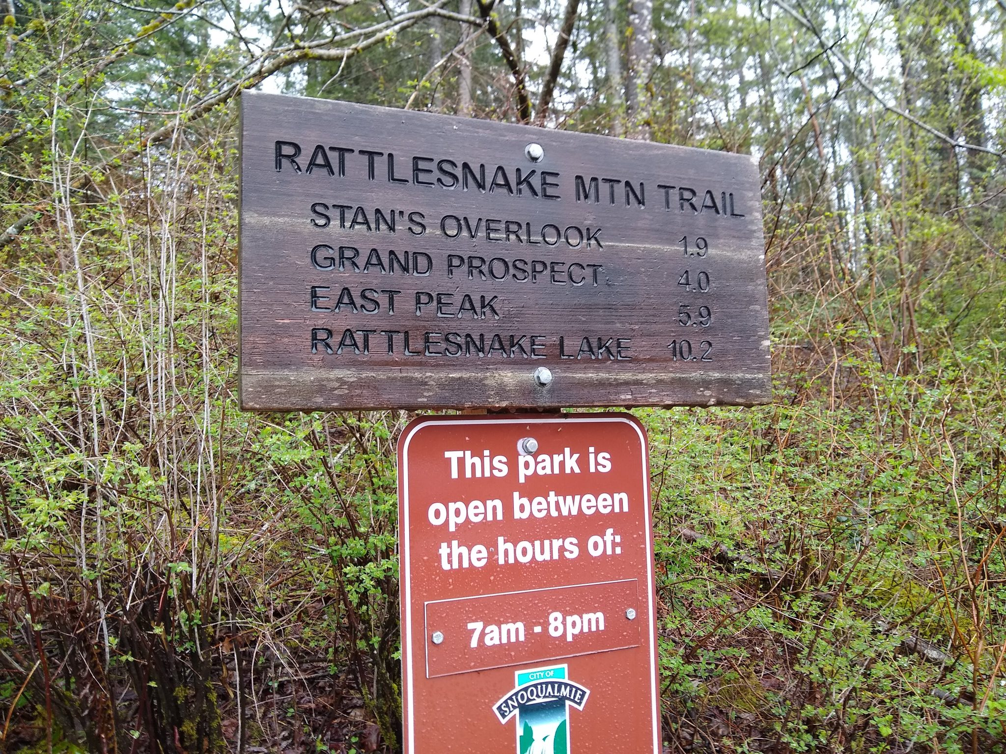 A wooden sign notes the distance to various destinations on the Rattlesnake Mountain Trail.