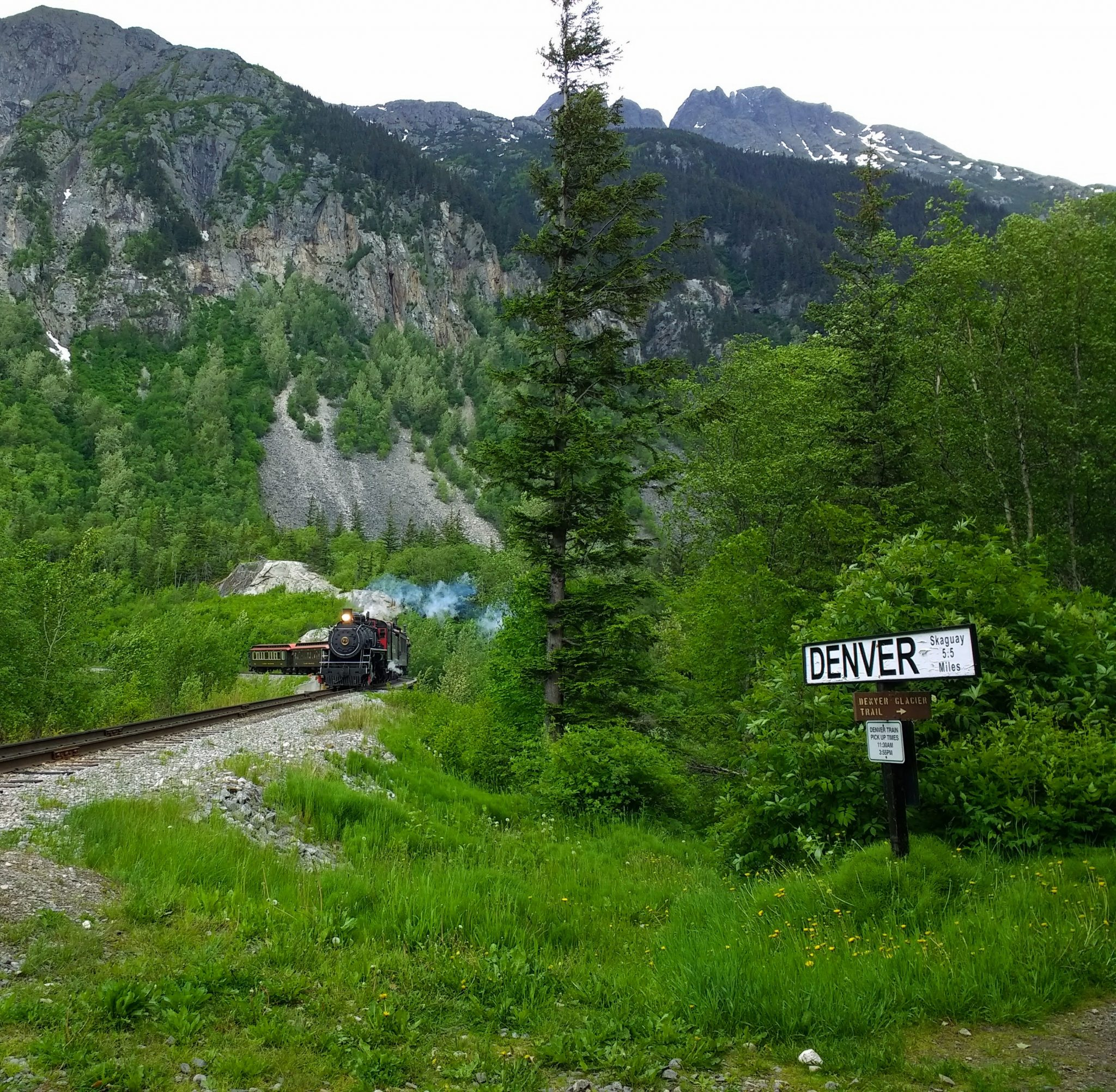 "A trail approaches on a remote track, surrounded by trees and mountains. A sign says ""Denver: Skagway 5.5 miles"""