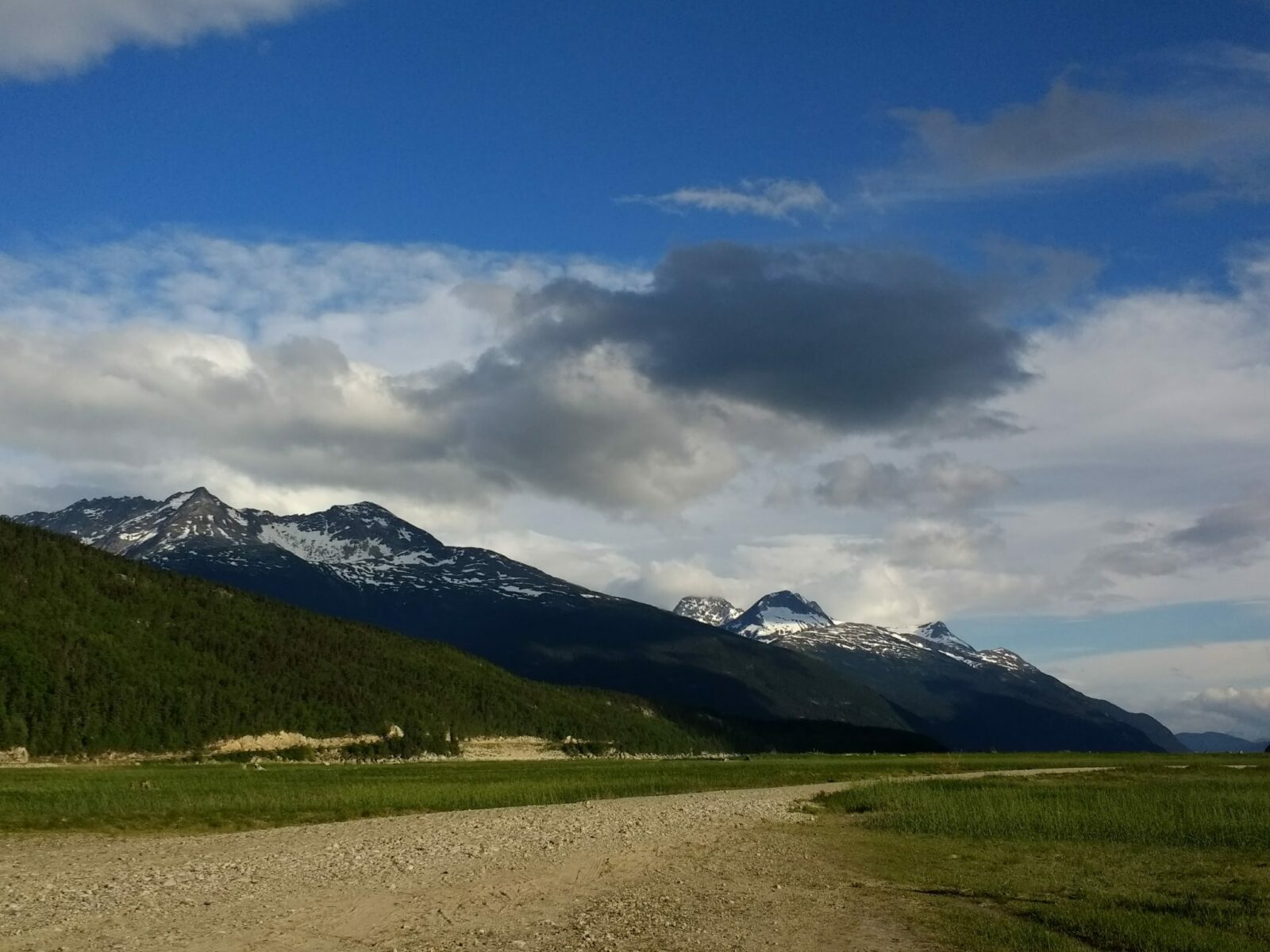 A wide flat gravel and grassy area surrounded by evergreen trees and high mountains near the Dyea campground in Alaska