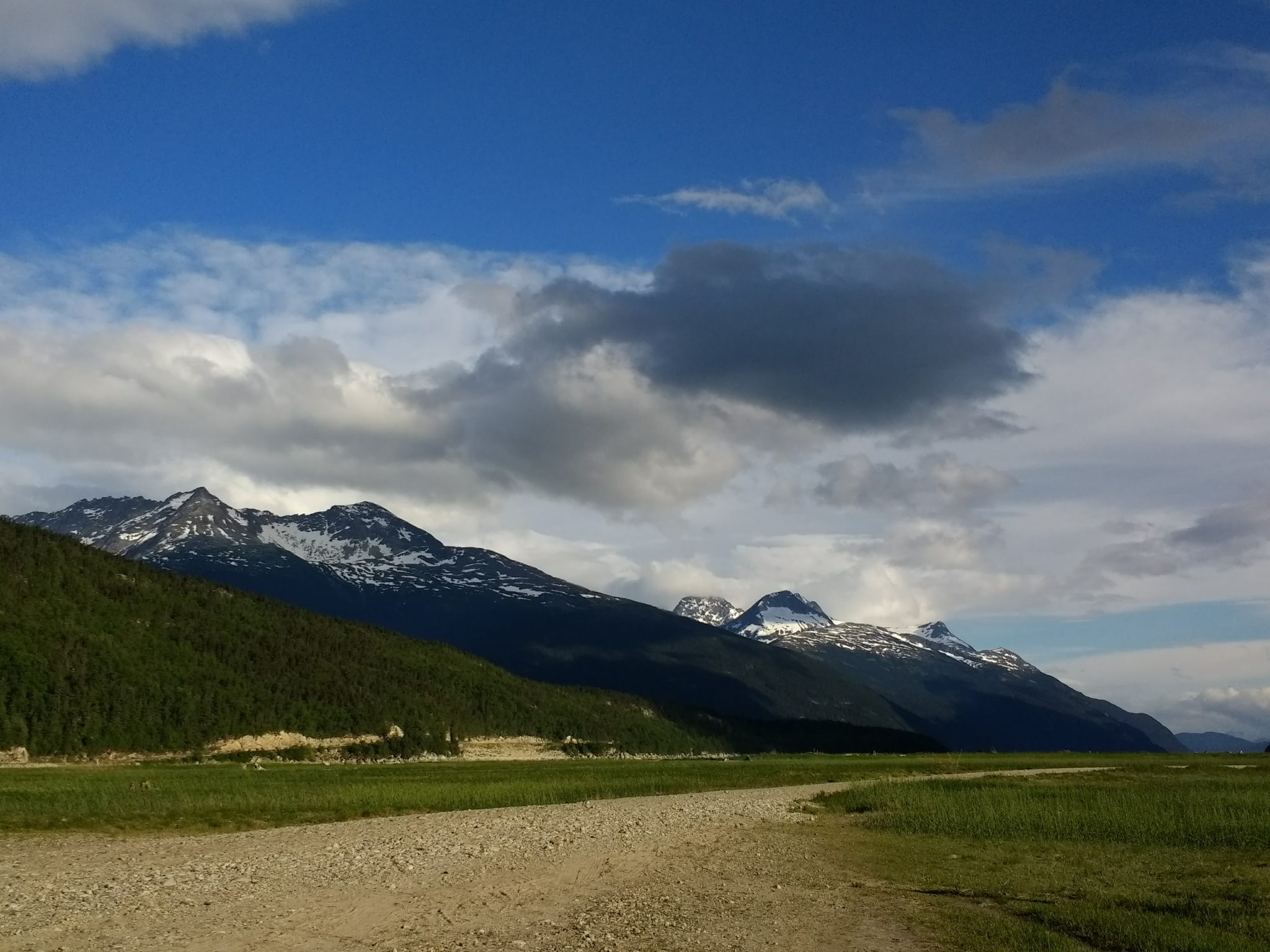 A gravel road through a meadow with snow capped mountains and partly sunny sky