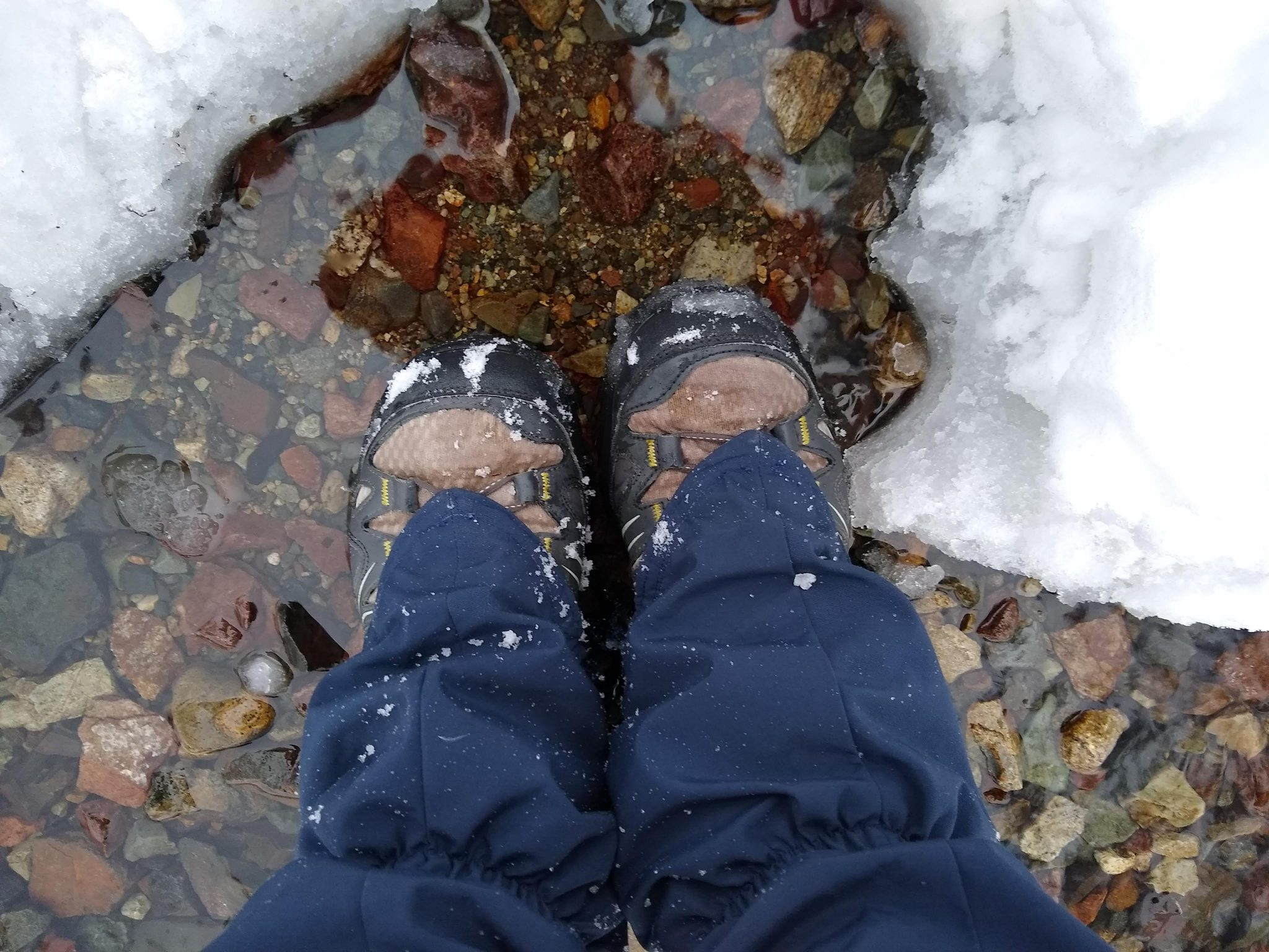 A person's lower leg and feet. They are standing in a puddle surrounded by snow. They are wearing waterproof shoes and gaiters to protect their feet and legs from getting wet