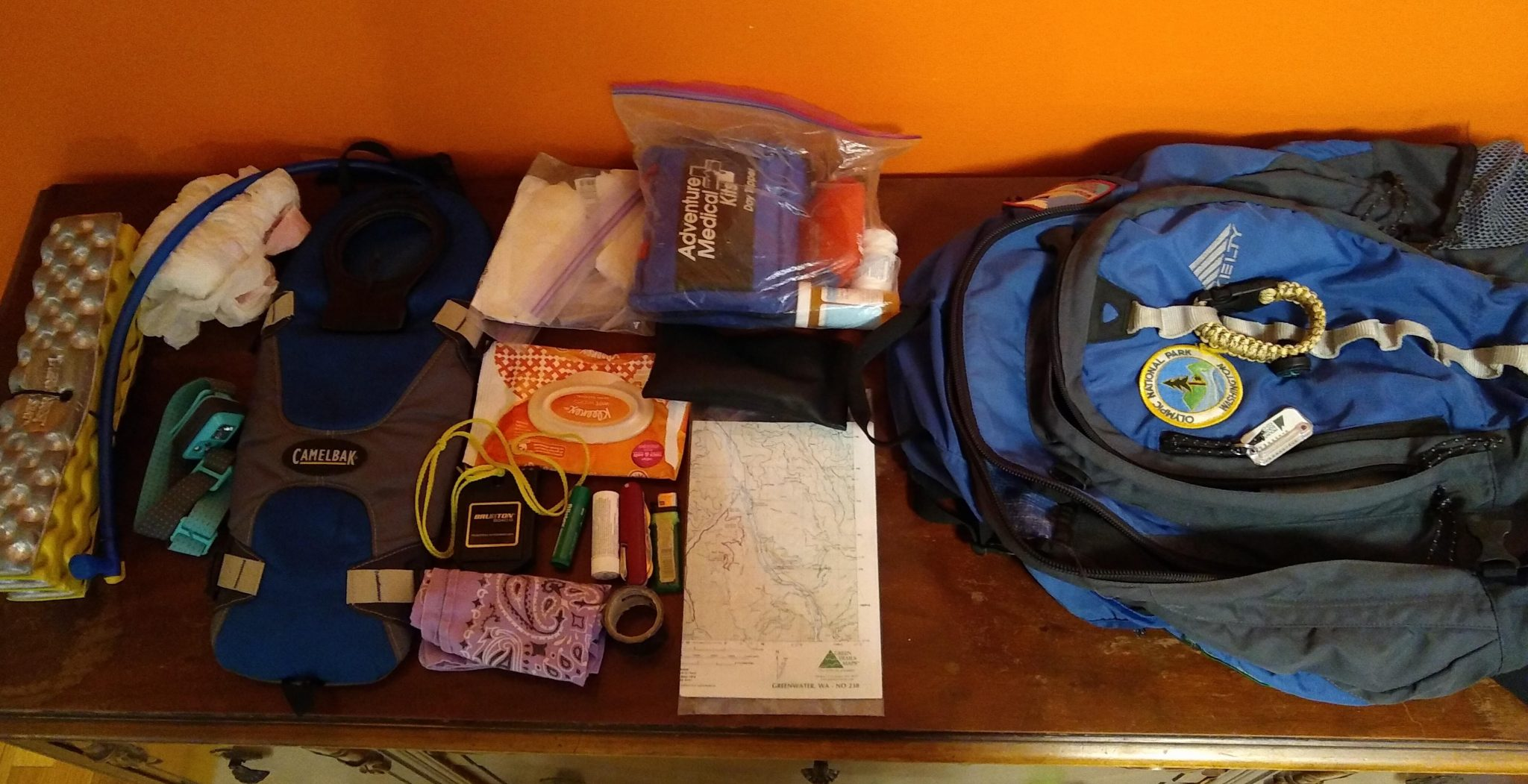 A backpack and some of it's contents spread out on a table including a map, first aid kit, water bladder, headlamp, bandana and plastic bag.