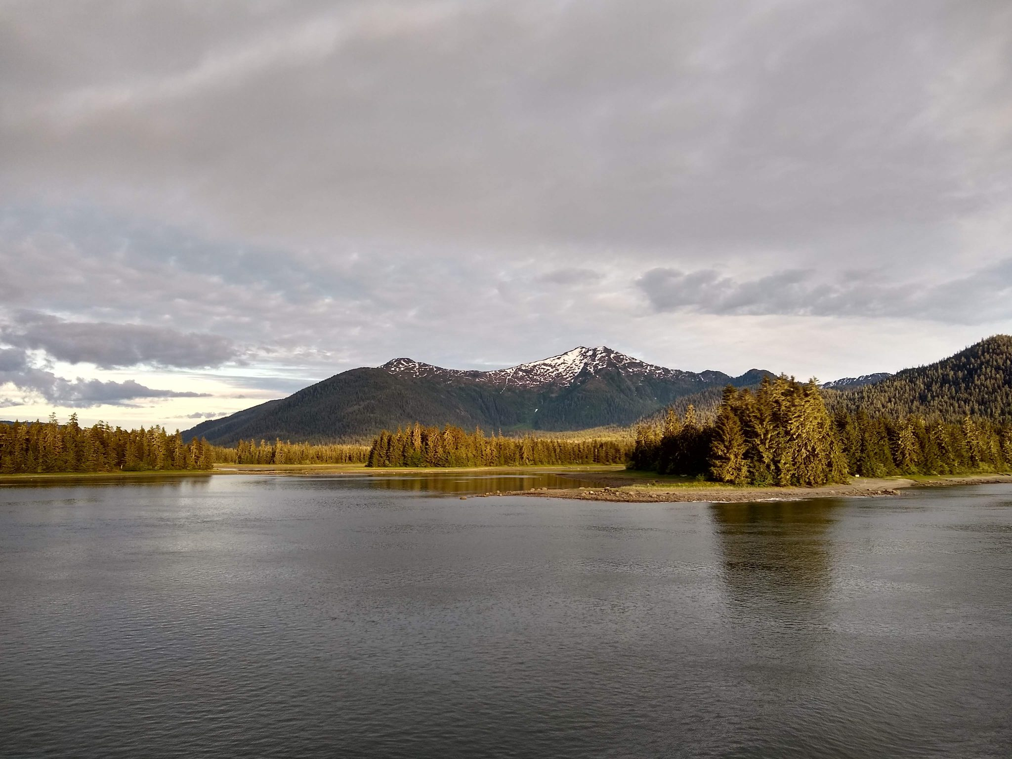Calm waters in the foreground, green trees and higher mountains with a bit of snow in the distance on a cloudy day