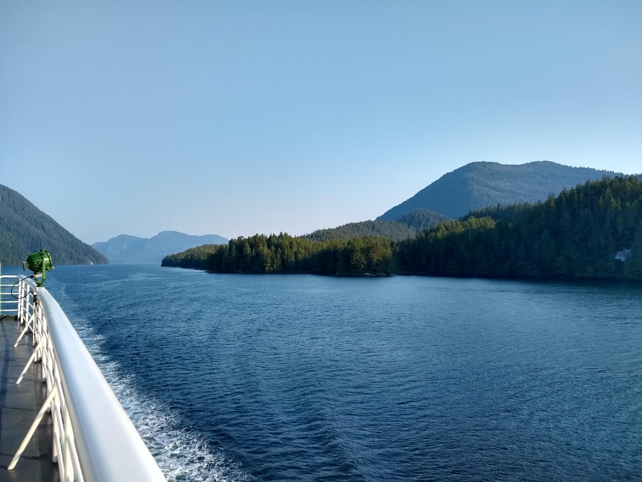 The railing and deck of the Alaska ferry are visible as it passes through a narrow channel between forests hills and mountains on a sunny day