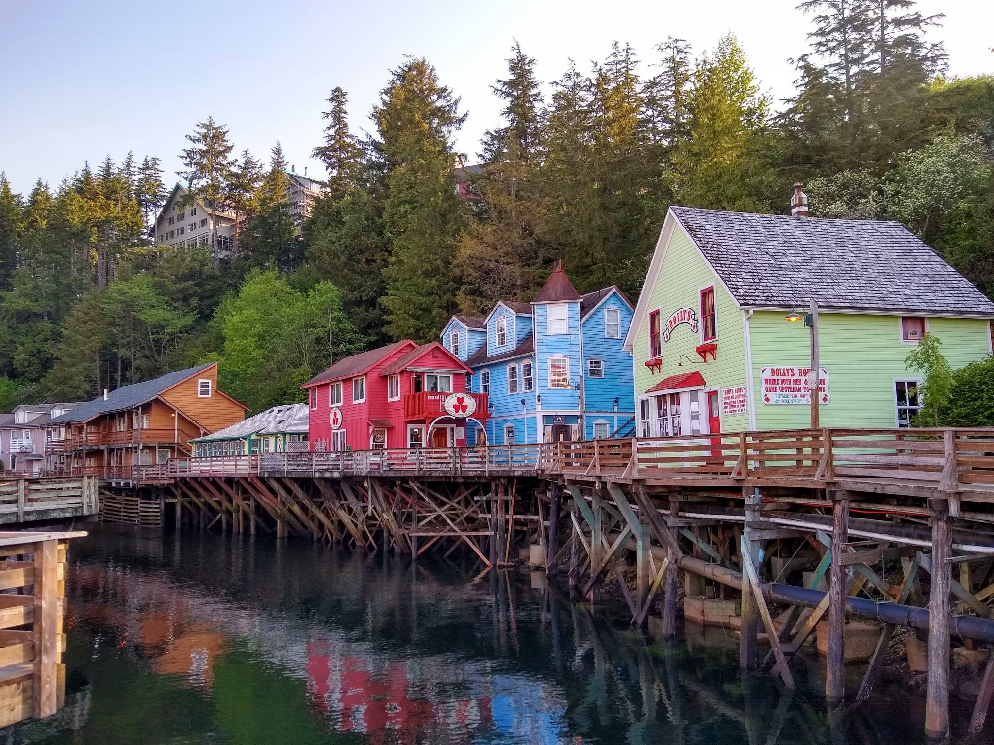 Brightly colored historic buildings are built on stilts against evergreen trees along Creek Street in Ketchikan, Alaska