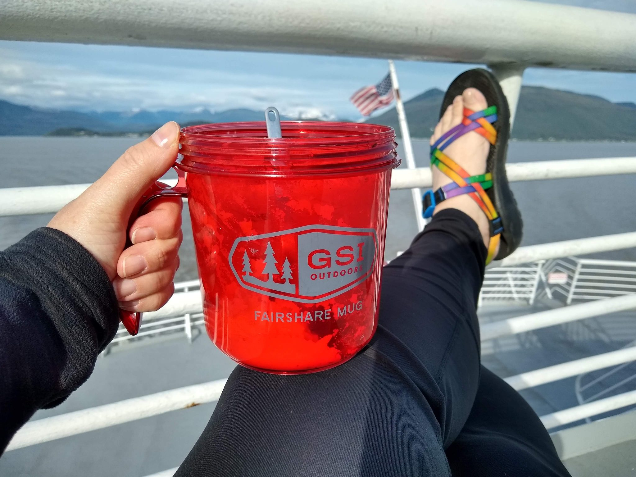 A woman is on the deck of a ship. We can see only her legs, feet and hand holding a red mug with food in it.