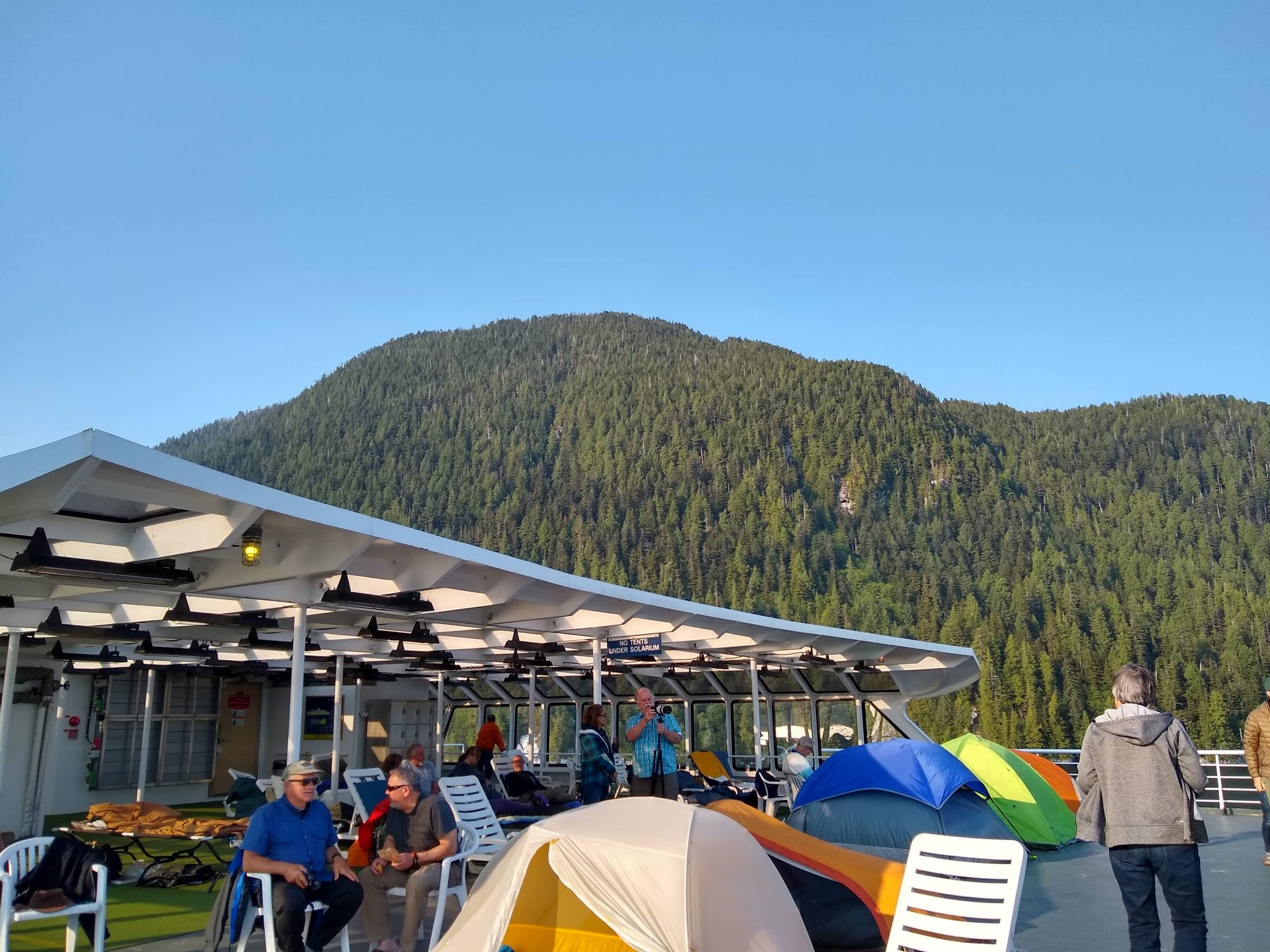 People on the top deck of the Alaska ferry. There are tents on the deck and sleeping bags under the solarium. The ferry is passing close to a forested hillside on a sunny day.