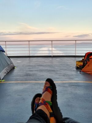 A woman's feet are visible in front of her. She is on the deck of a ship at dusk. There are two tents visible on the deck on either side of her.