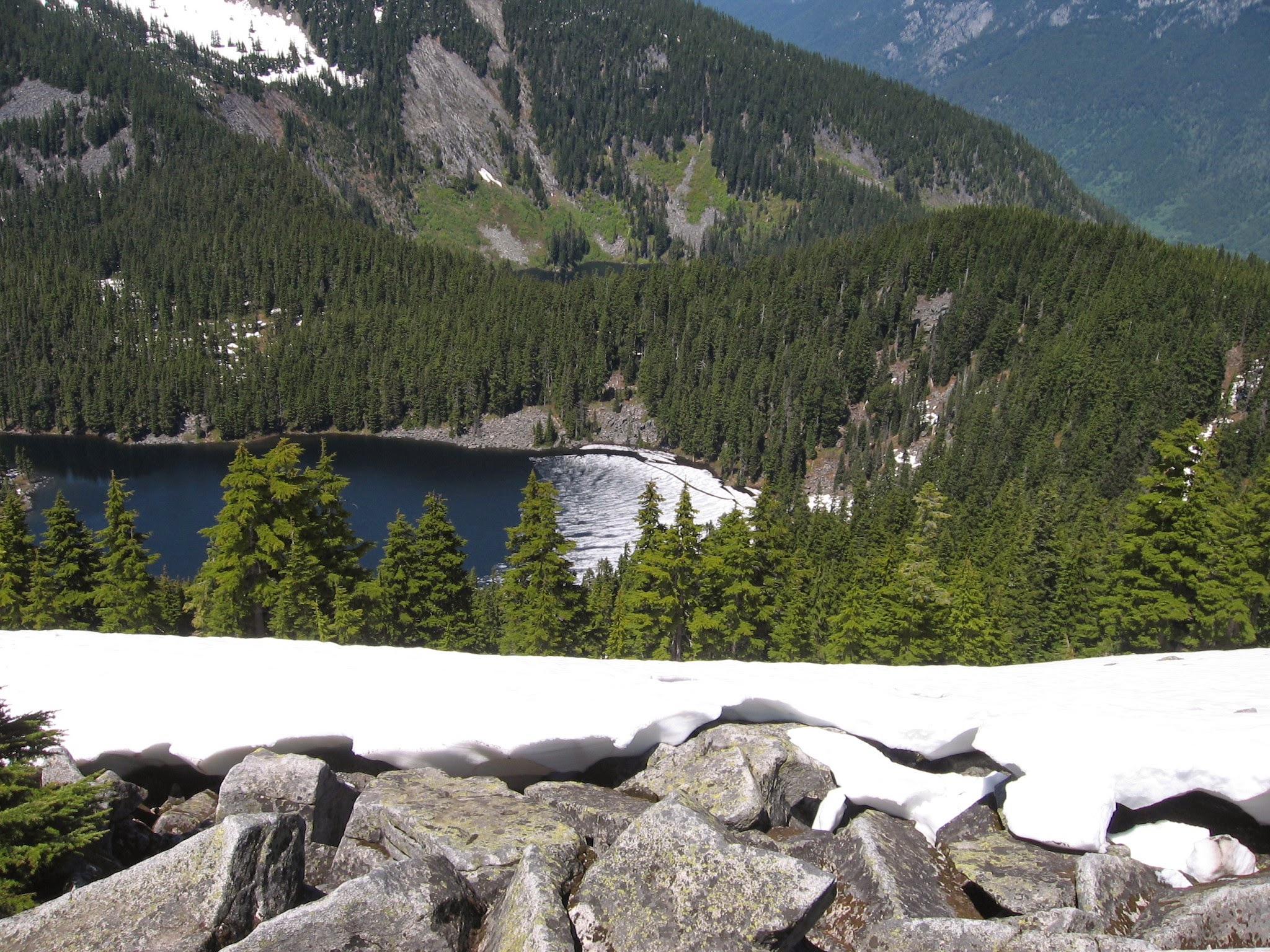 Snow covered rocks in the foreground, with trees and an alpine lake and other mountains in the background