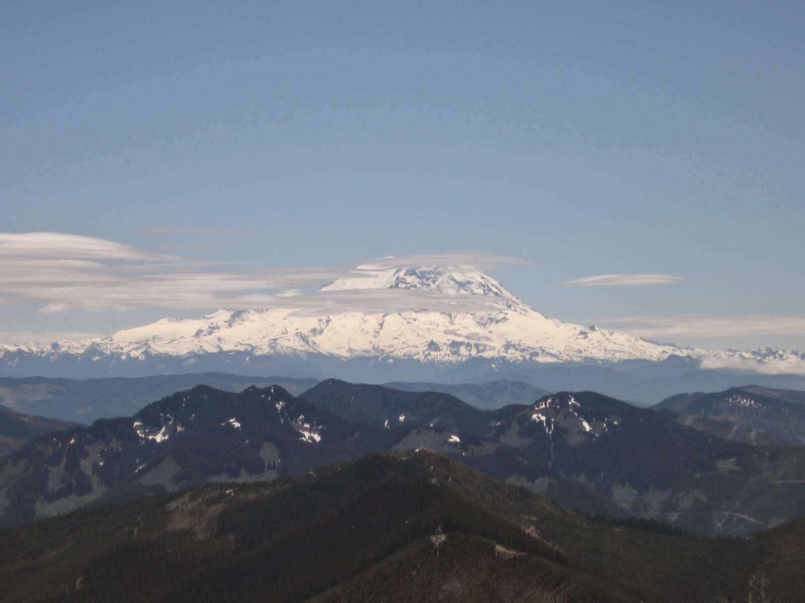 Mt Rainier, a high snow covered mountain, in the background surrounded by a few clouds on an otherwise sunny day. Smaller mountains are in the foreground from Bandera Mountain, one of the best hikes in Washington