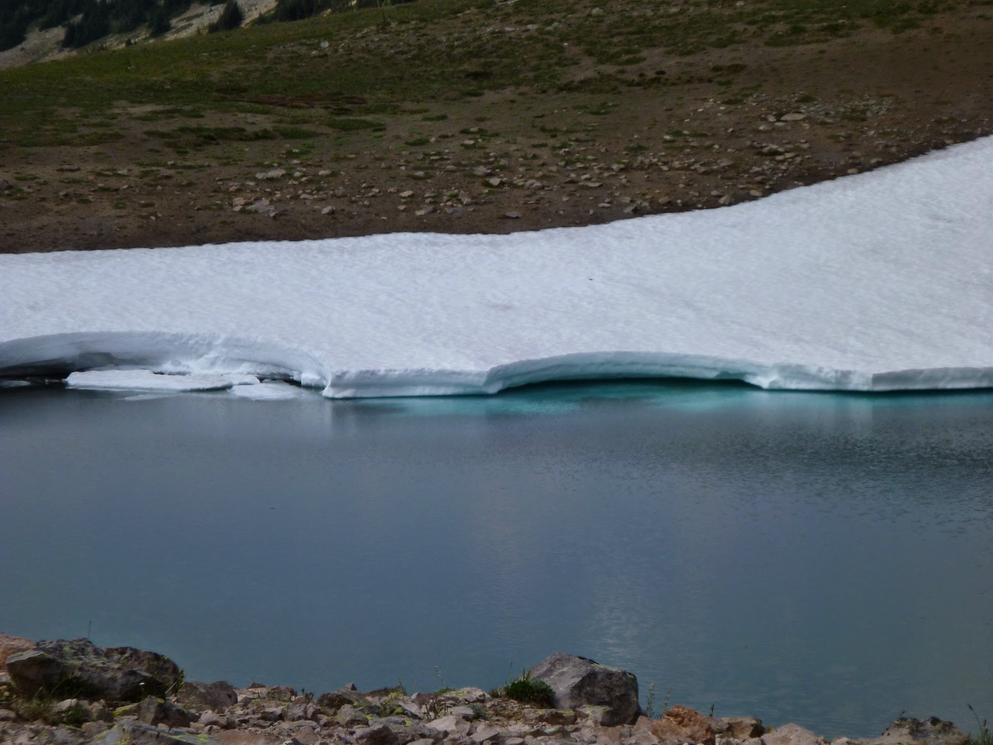 A small blue lake partially surrounded by ice and snow. Bare rocks are visible in the foreground and background