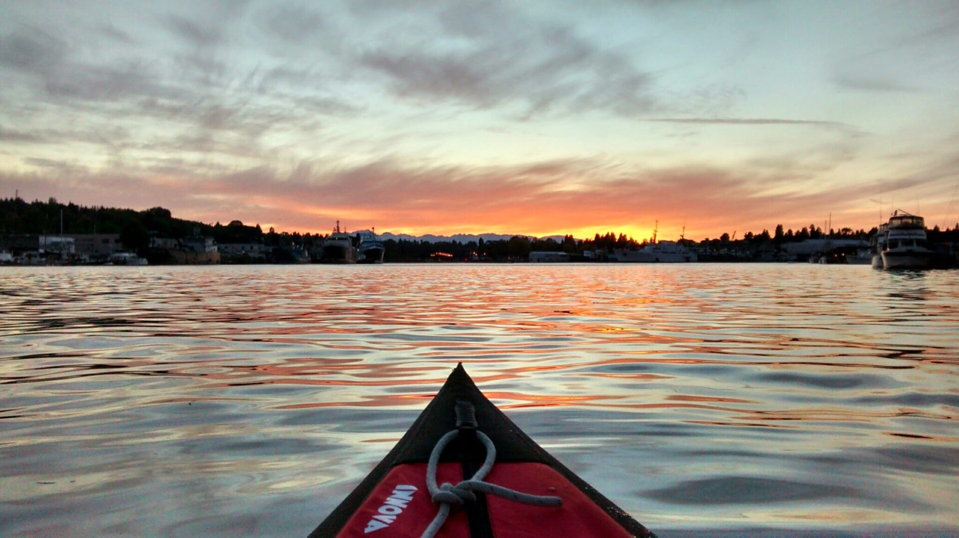 The bow of a kayak in the water just after sunset. There are boats and tree lined hills around the lake