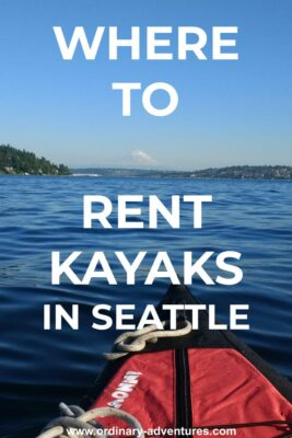 A kayak bow on a lake surrounded by forested hills with houses. Mt Rainier is in the background on a sunny summer day. Text reads: Where to Rent kayaks in Seattle