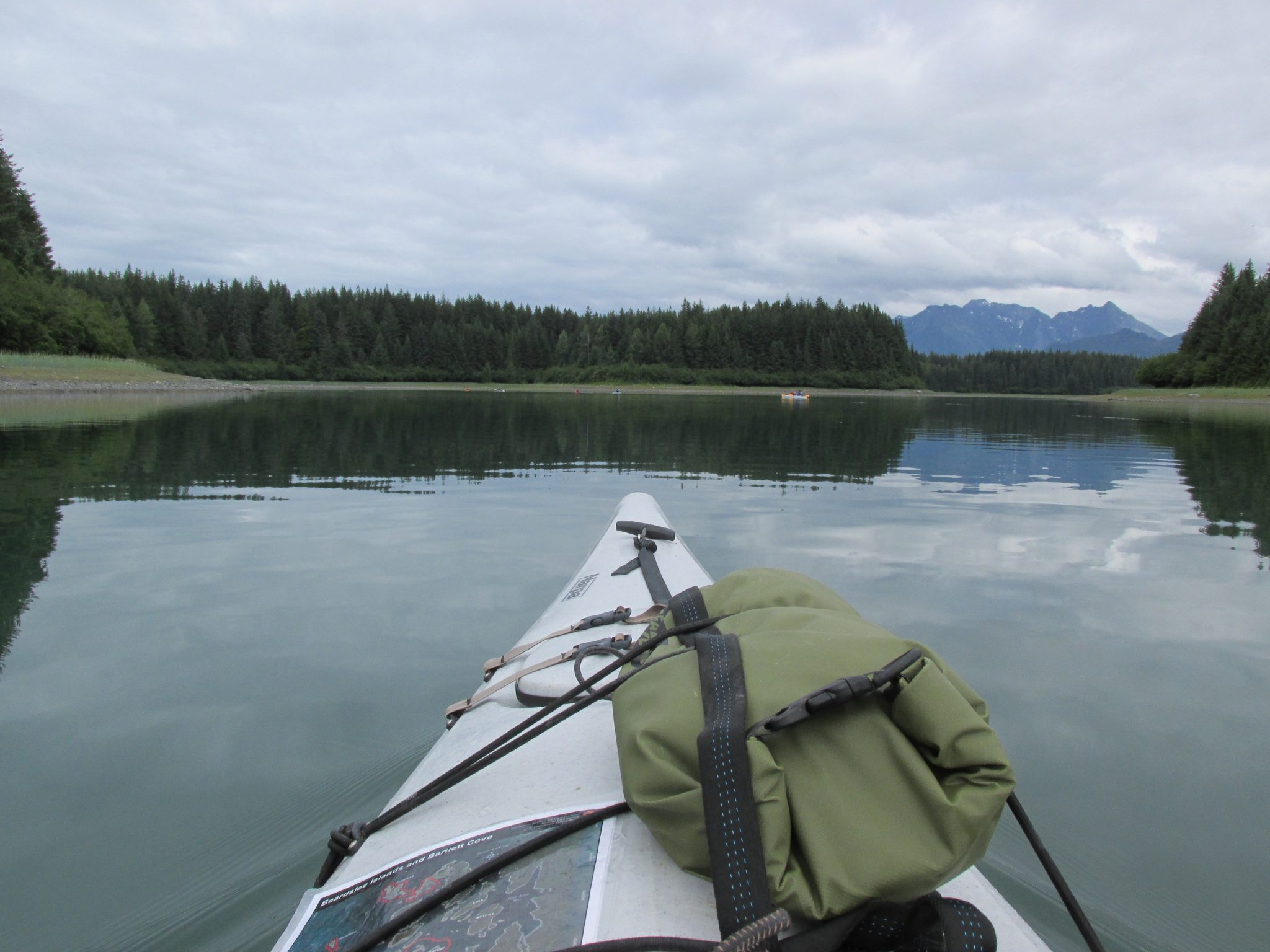 The front of a kayak with a map and dry bag tied to it. The water is calm, there are forested islands around it and some distant mountains on an overcast day