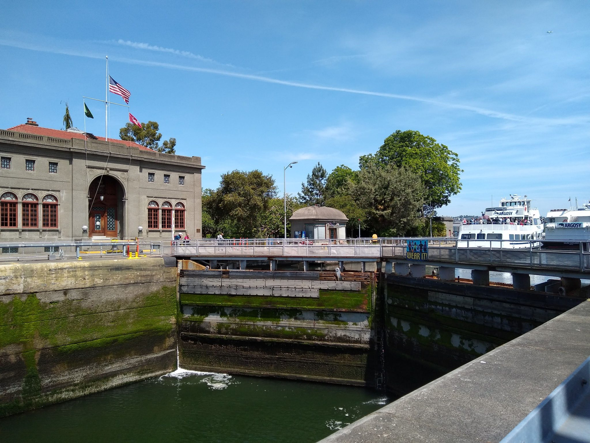 A large stone building with flags on the left. A lock with low water in front and higher water in the back with a boat in it.