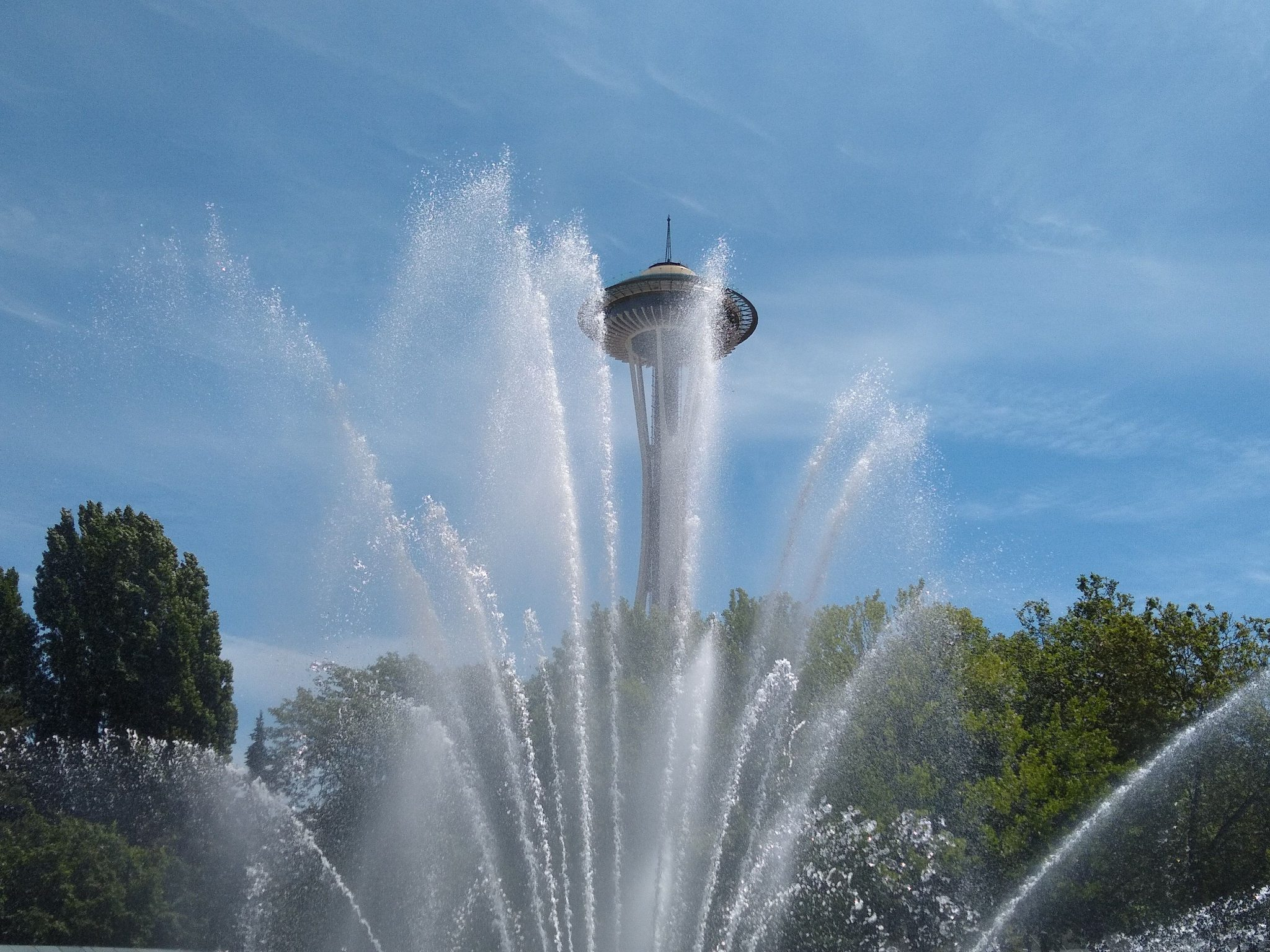 A fountain is spraying in front of green trees and the Space Needle.
