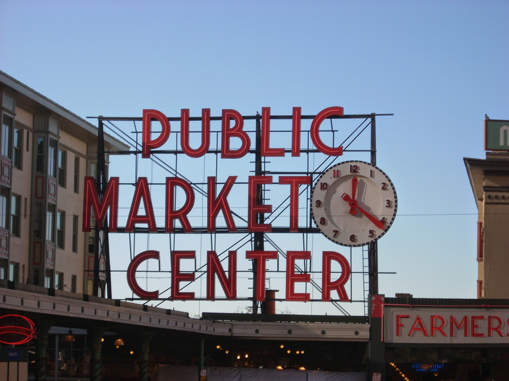 The Public Market Center sign in Seattle. The sign has large red letters and a red and white clock.