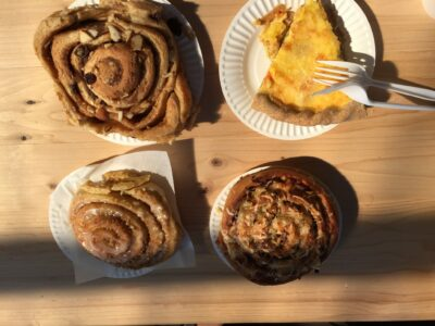 There are four pastries on a picnic table outside in the sun. There are three cinnamon rolls and one quiche with a fork