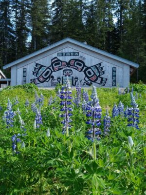 A wooden building with Tlingit art on the side. Purple wildflowers are in the foreground