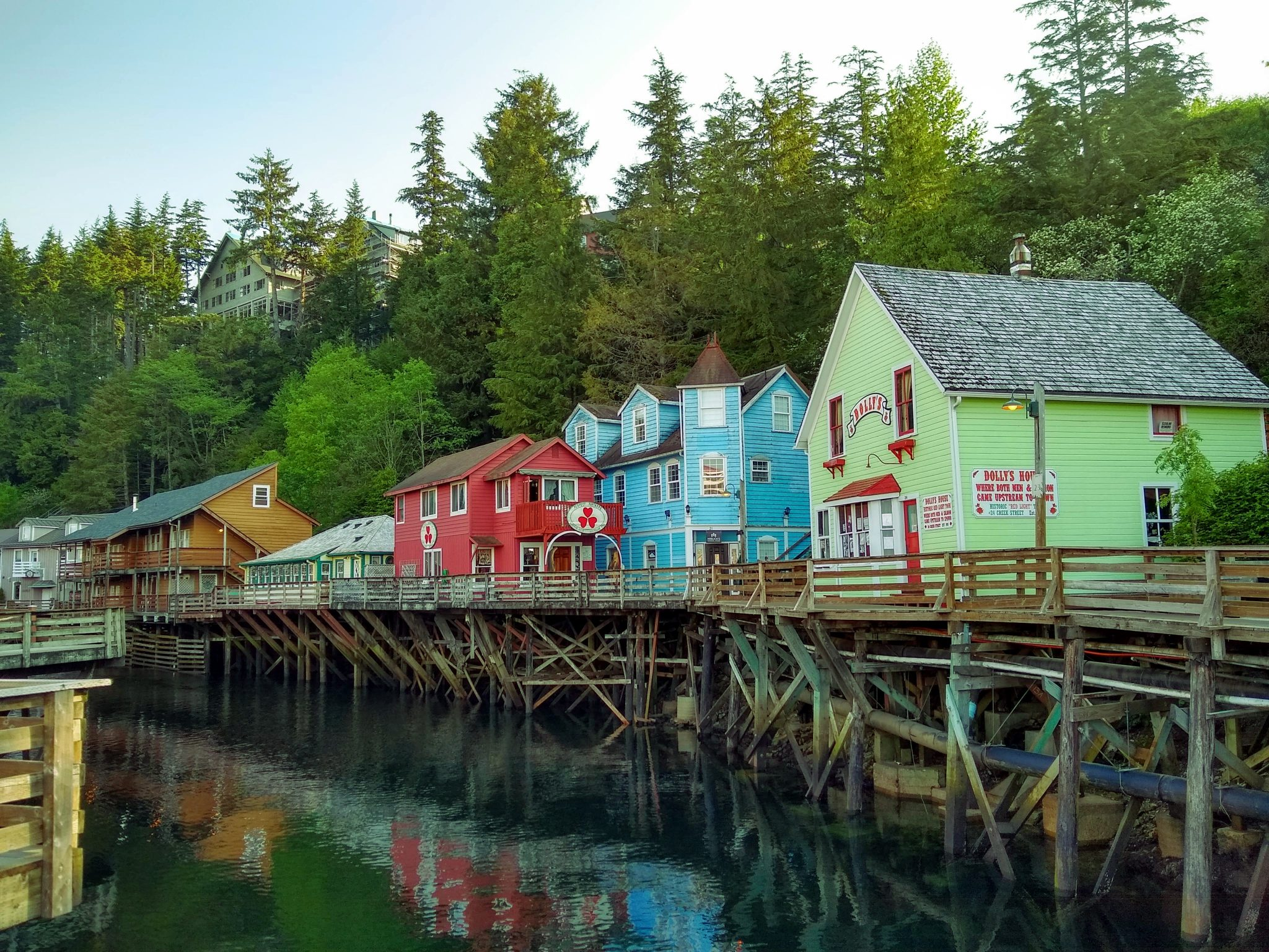 Several brightly colored historic wooden buildings are built on wooden piers above the water. The water is calm and the buildings are reflected in it. There are evergreen trees behind the buildings on the hill