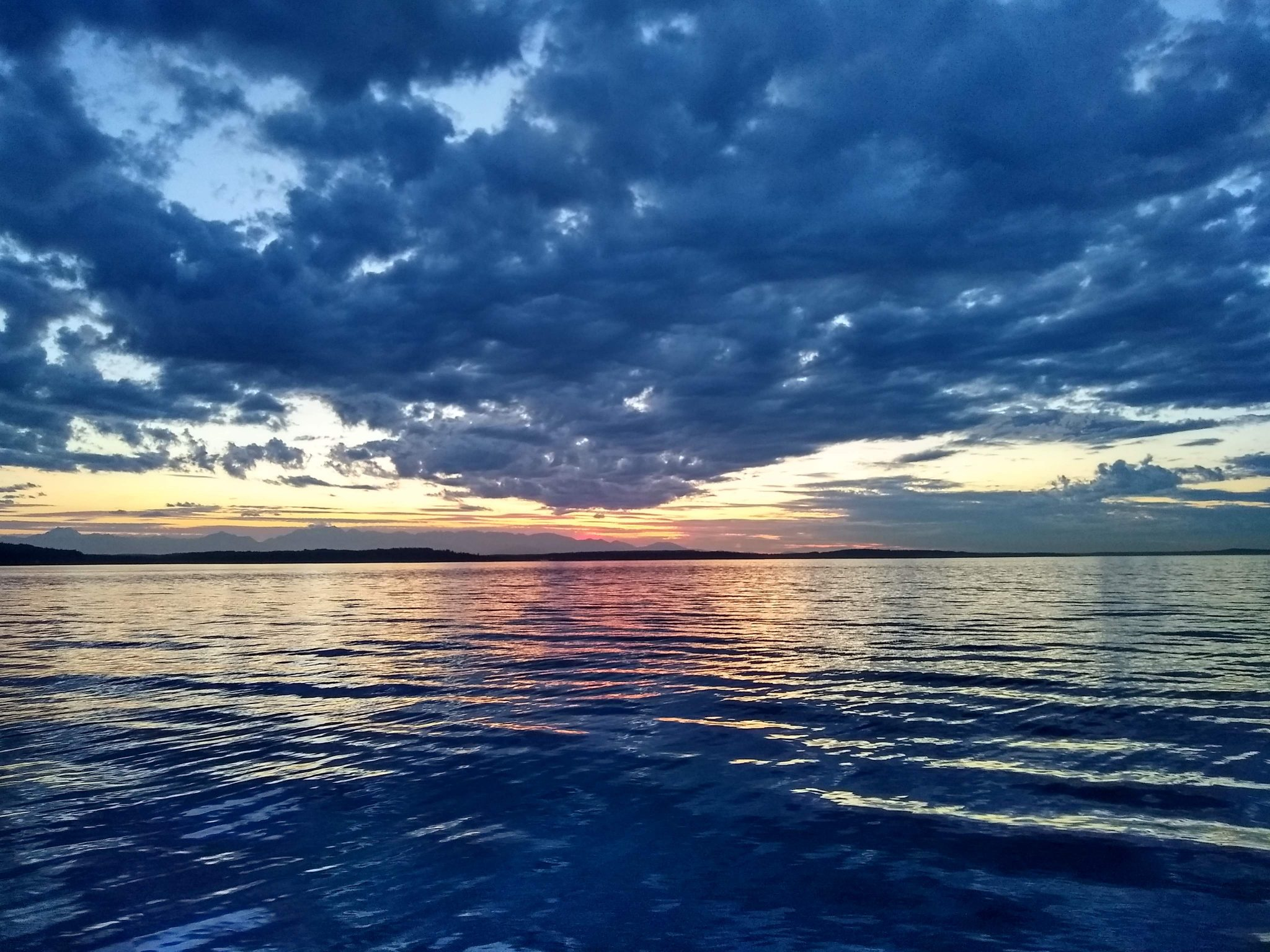 A sunset with lots of clouds and calm water. The sunset is pink and yellow