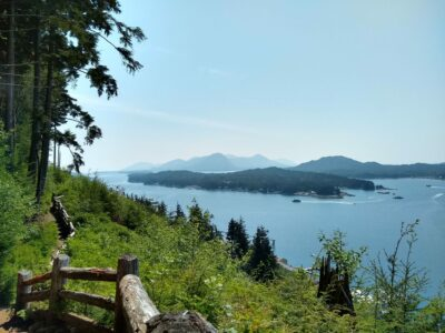 on a sunny day in Ketchikan Alaska, a trail goes along the side of the hill. A wooden fence is along the trail and it is green with shrubs and trees. Below is a busy waterway with boats and many forested islands.