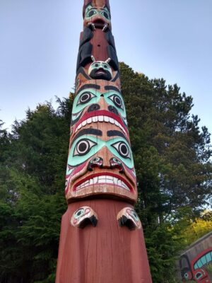 A close up of a totem pole whose top and bottom go beyond the frame. In the background is a tall tree
