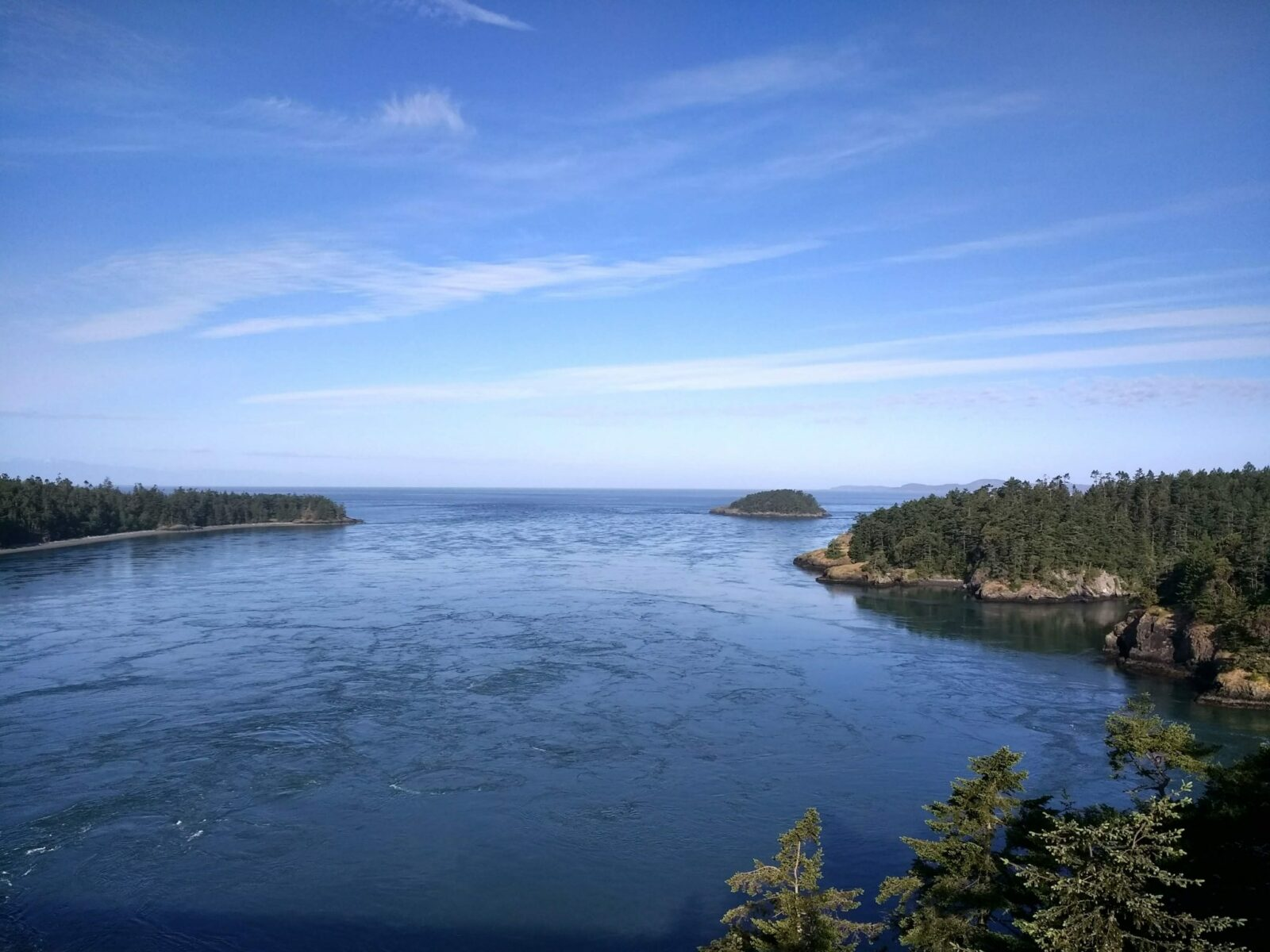 A view from a high bridge on a sunny day. There is churning water below and forested hillsides on both sides as well as islands in the distance